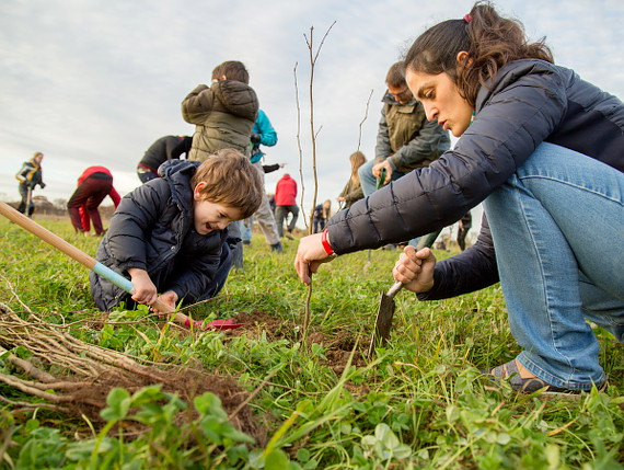 Young boy and lady planting tree at Heartwood Forest